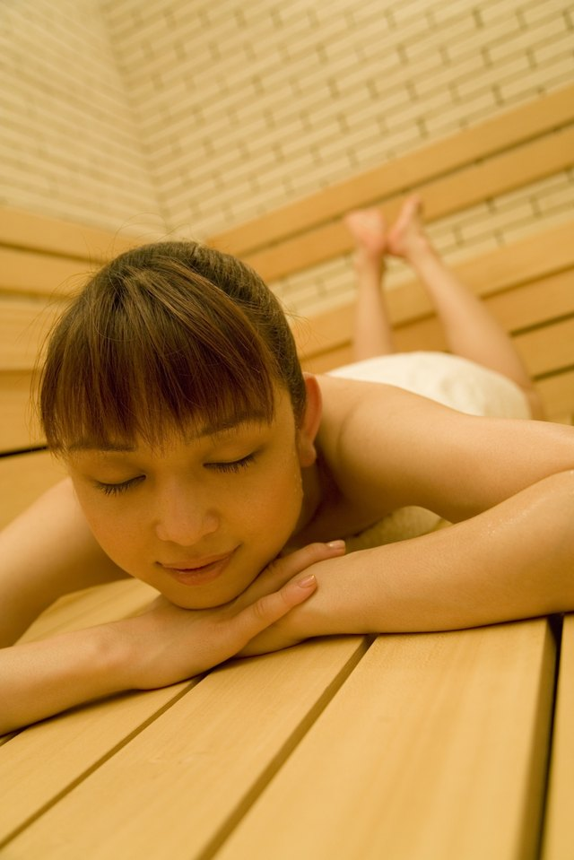 Woman relaxing in sauna, eyes closed, front view, differential focus