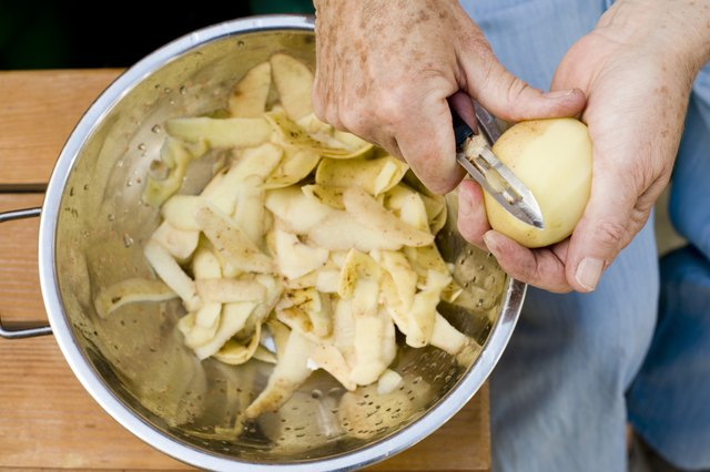 Person's hands peeling potatoes