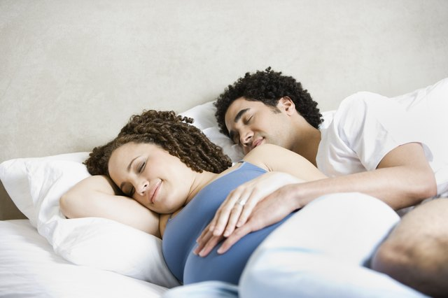 Pregnant African couple sleeping in bed
