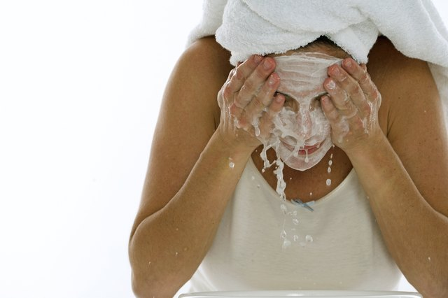 Young woman splashing water on her face