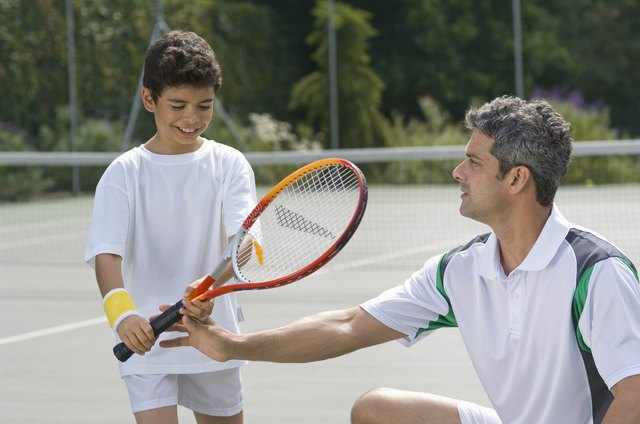 Man teaching boy to play tennis