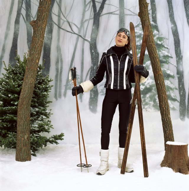 Woman with old skis and ski poles