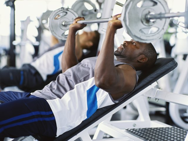 Two mid adult men exercising in a gym with weights