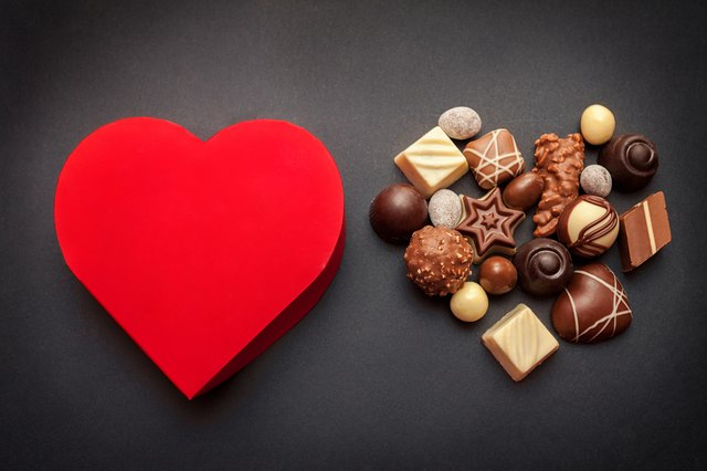 Red heart shaped box with chocolate pralines on dark background