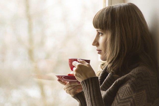 Beautiful girl drinking Coffee or Tea near Window