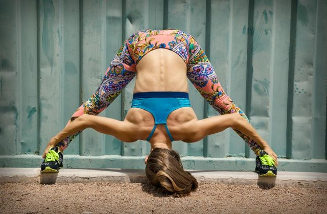 Fit woman doing exercise near the wall outdoor