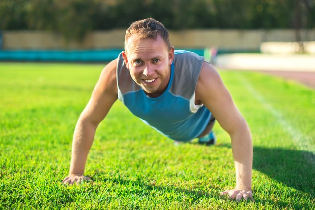 sport man stretching at the park, doing push-ups on  grass