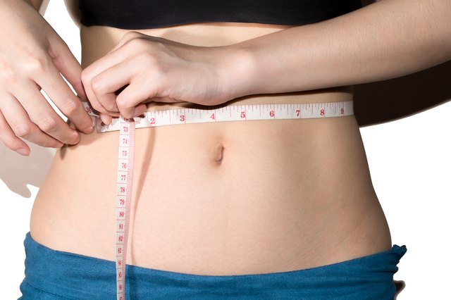 Young slim woman measuring waist circumference