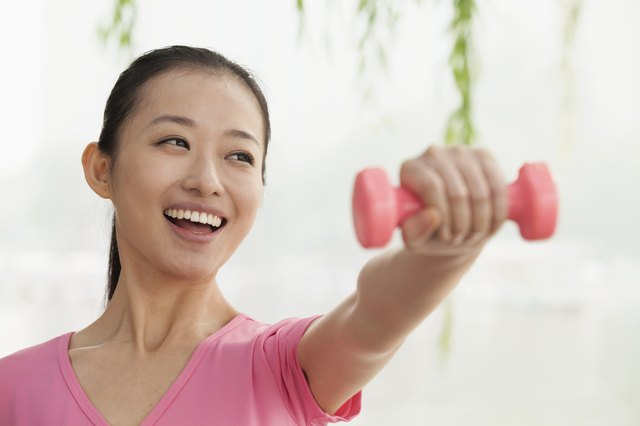 Young Woman Lifting Weights in the Park