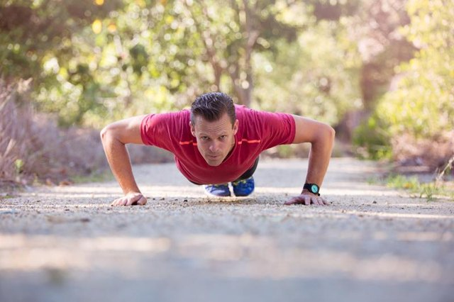 A determined young man does a pushup on a gravel footpath.