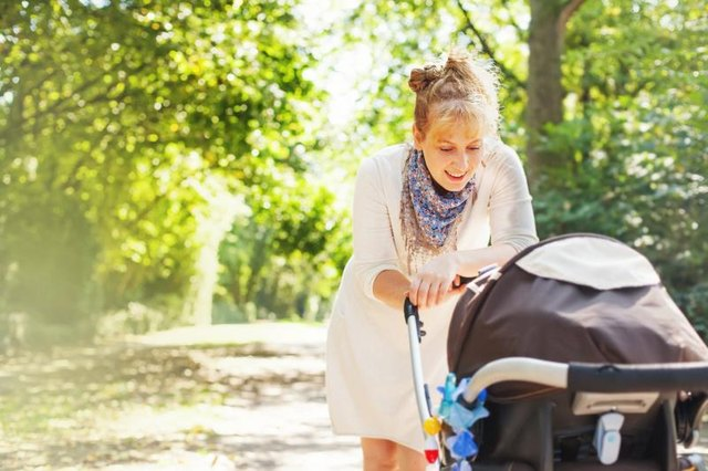 mother walking with baby in stroller