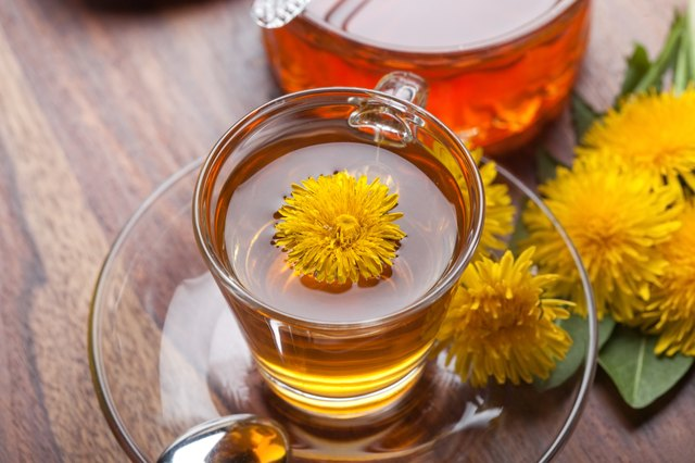 herbal tea of dandelion with honey, blossoms on wooden table