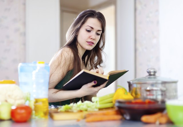 beautiful housewife cooking with cookbook