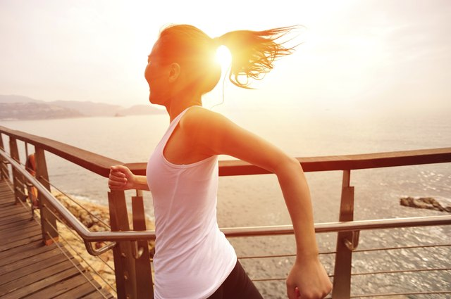 healthy lifestyle asian woman running at wooden trail seaside
