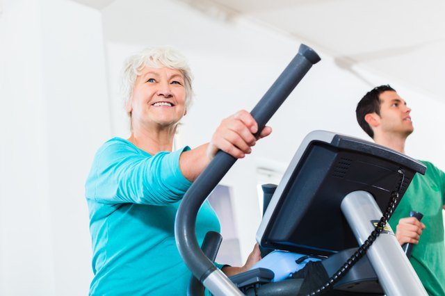 Senior woman on elliptical trainer exercising in gym