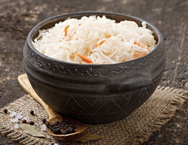 Sauerkraut with carrot in wooden bowl