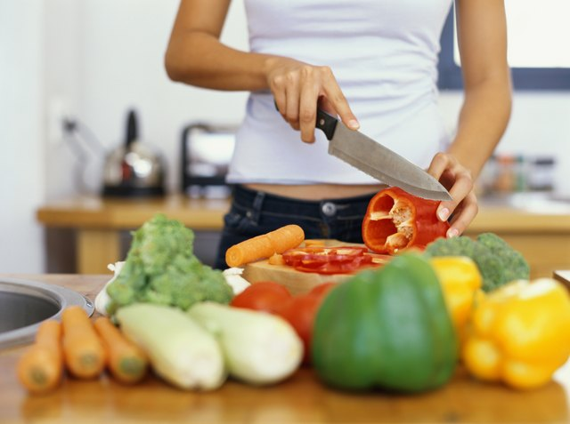mid section view of a young woman cutting red bell pepper in the kitchen