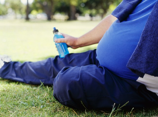 side profile of a mid adult man holding a water bottle in a park