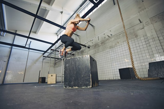 Fit woman is performing box jumps at gym