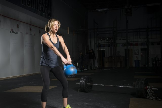 Woman swinging a kettle bell in a gym.