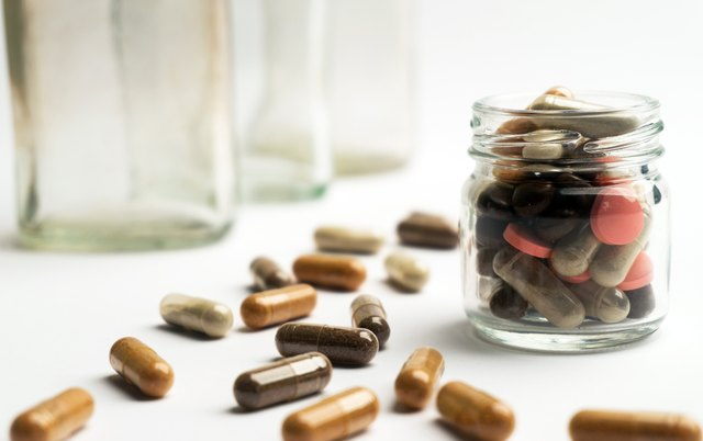 Different pills and capsules in glass jar on white background.