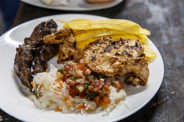 traditional nicaraguan cuisine, roast meat, salad and fried banana.