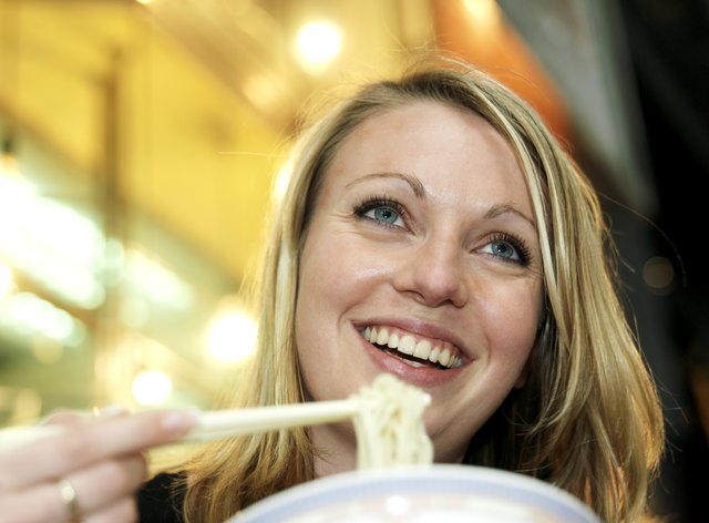 Woman eating noodles, smiling, low angle view