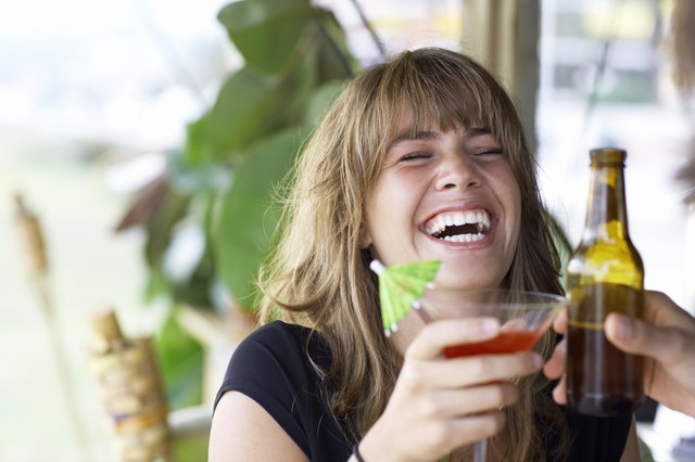 Young woman toasting drink with friend, laughing, close-up