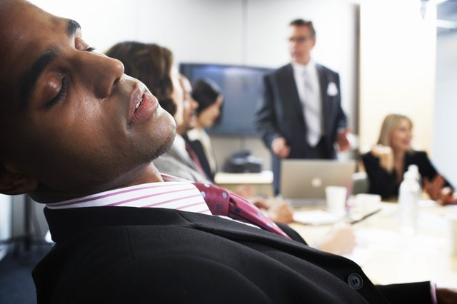 Businessman in meeting, eyes closed, close-up