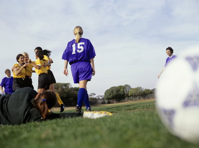 Young women footballers on pitch, rejoicing victory, surface view