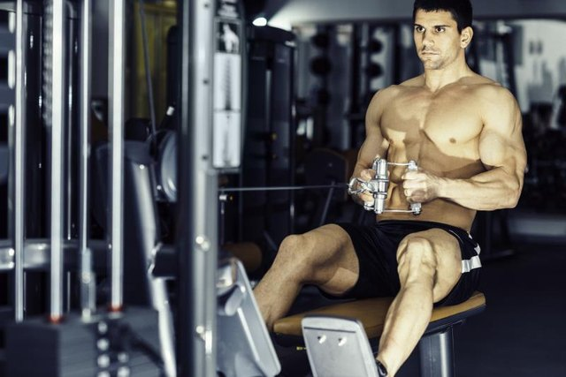 Man exercising back muscles on rowing machineMuscular young man exercising on rowing machine in modern gym.