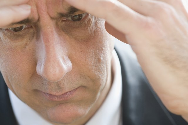 Close-up of businessman touching forehead