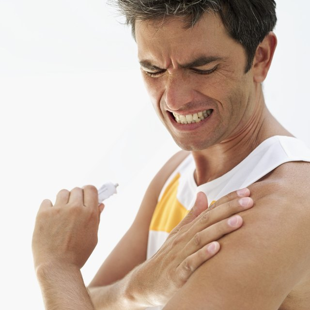 side profile of a mid adult man applying ointment on his shoulder