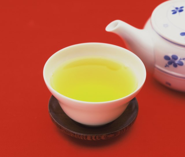 Cup of green tea, red background