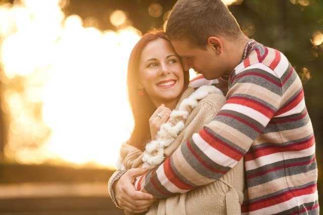 Happy young couple embracing while walking in a park on  a sunny autumn day