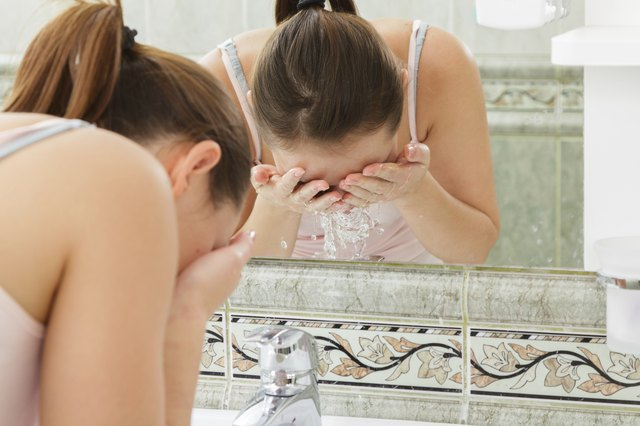 Young woman washing her face with clean water