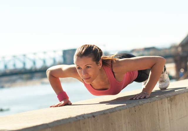 Young sporty woman doing push-ups in sunny day on riverbank.