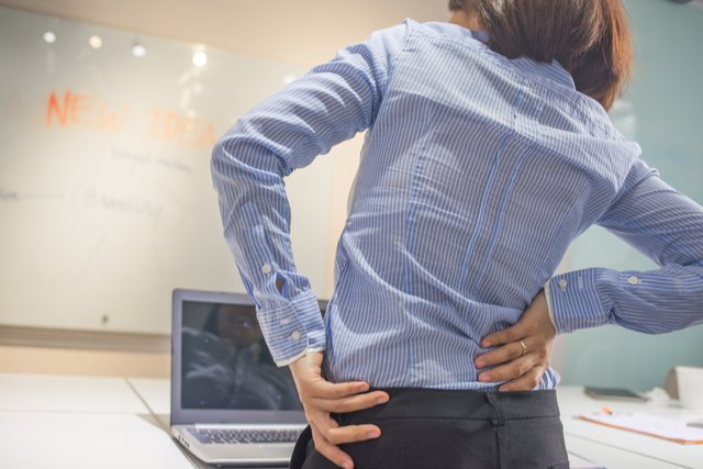 Woman doing some simple exercise for her back at office