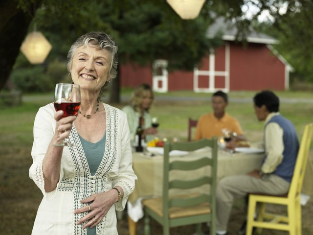 People dining in yard, focus on woman with red wine in foreground