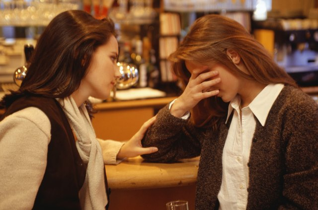 Young woman comforting friend at bar