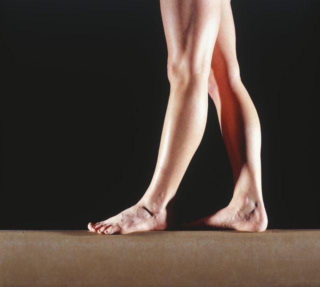 Female gymnast walking on balance beam, low section