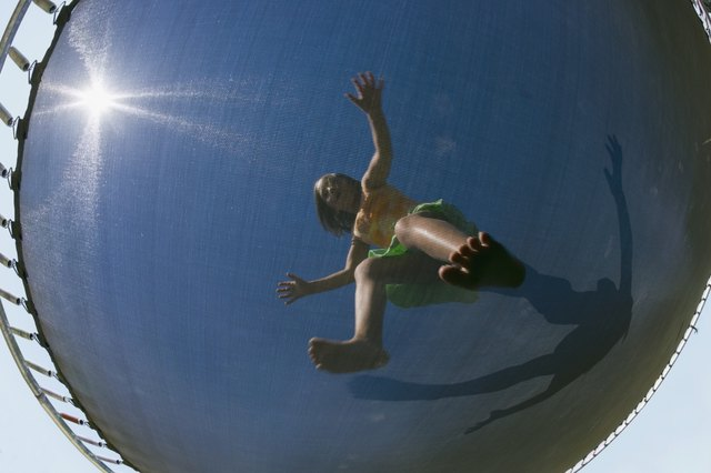 Low angle view through trampoline of girl