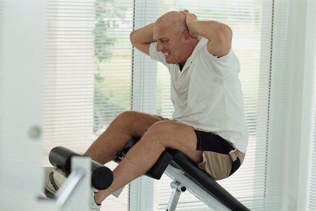 Senior man doing sit-ups in a gym