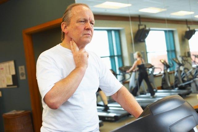 Man checking his pulse on treadmill at gym