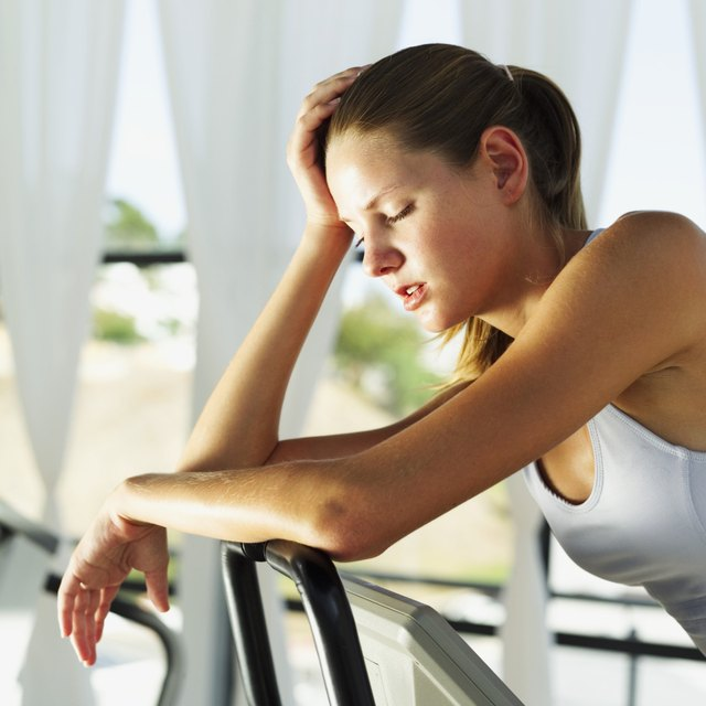 side profile of a young woman resting on the handlebars of an exercise bike