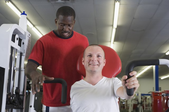 One-armed man in gym with trainer