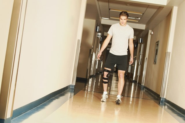 A young man walking with a knee brace in a hospital
