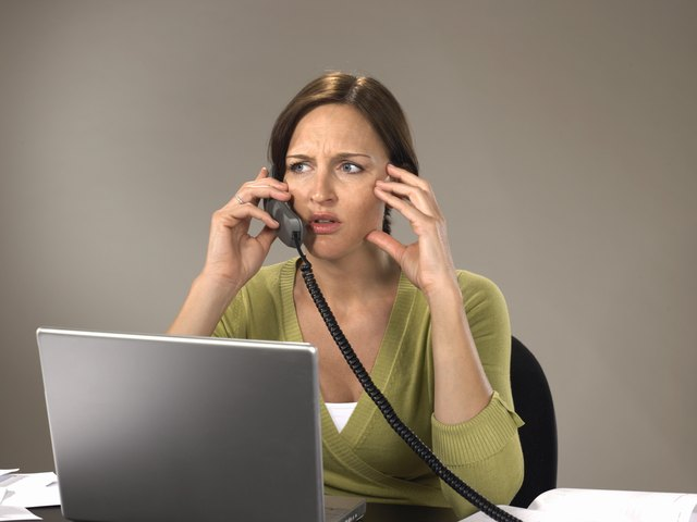 Woman sitting at laptop using telephone, frowning