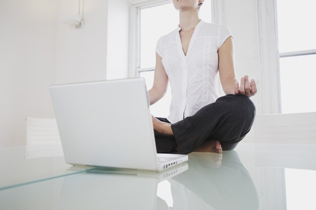 Mid-adult woman in lotus pose or yoga pose in office