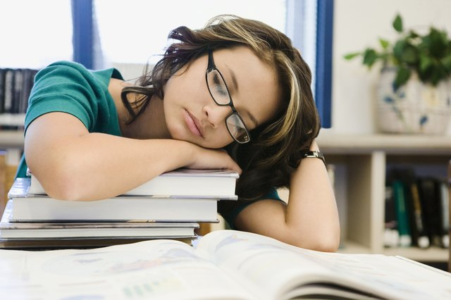 High School Student Sleeping on a Stack of Books